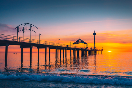 People walking along Brighton Jetty at sunset. South Australia Stock Photo