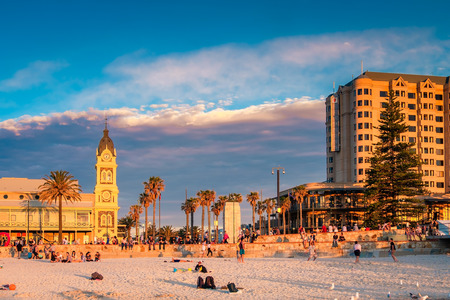 Adelaide, Australia - August 29, 2016: People meeting sunset at Glenelg Beach on a warm evening. Viewed towards Moseley Square and Pioneer memorial. Editorial