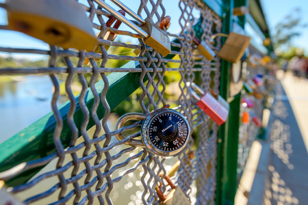 guardrails: Adelaide, Australia - April 14, 2017: Love locks hooked up to guardrails of Adelaide University Bridge across Torrens river in North Adelaide on a bright day