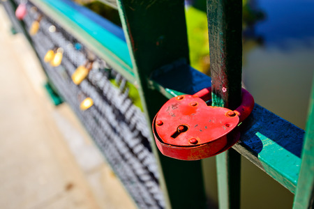 Vintage red love lock hanging on the fence as a symbol of loyalty and eternal love