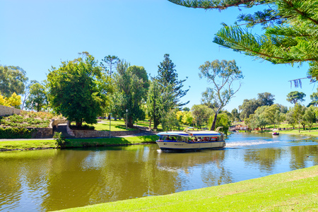 downstream: Adelaide, Australia - April 14, 2017: Iconic Pop-Eye boat with people on board traveling downstream in Torrens river near Adelaide CBD on a bright day