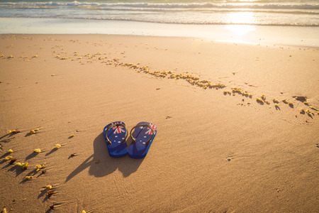 swimming shoes: Thongs with Australian flag on the beach at sunset