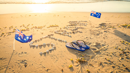 Straya text drawn using shells on sand with flags and thongs. Straya is an abbreviation of Australia