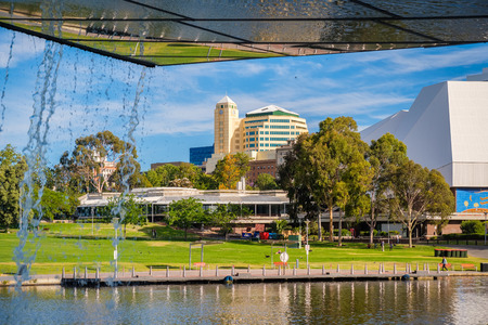 riverbank: Adelaide, Australia - December 2, 2016: Adelaide city centre viewed from under the foot bridge in Elder Park on a bright day Editorial