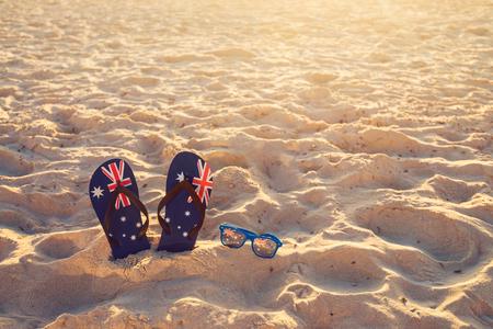 Thongs en zonnebril in zand op een strand, Australië dag concept Stockfoto