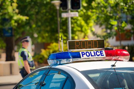 Zuid-Australische politieauto op straat in Adelaide met politieagent op de achtergrond