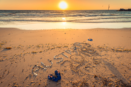 Australia 2018 text with thongs, flag and sunglasses on beach at sunset