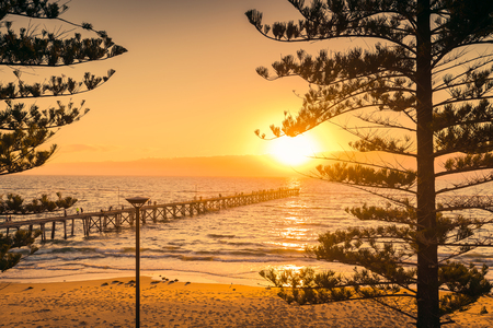 Port Noarlunga beach jetty with people at sunset, South Australia Stock Photo
