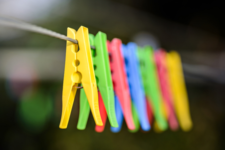 Colorful pegs hanging on clothesline Stock Photo