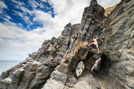 Man climbing up rock at Rapid Bay, South Australia Stock Photo