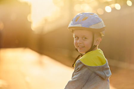 Smiling aussie boy wearing helmet and riding his bicycle a day in Glenelg, South Australia Stock Photo
