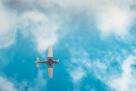 Aerobatic airplane flying high in blue sky viewed from the ground 免版税图像