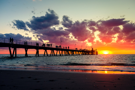People walking along Glenelg pier during dramatic sunset in South Australia