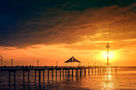 Iconic Brighton jetty with people silhouettes enjoying dramatic sunset, South Australia