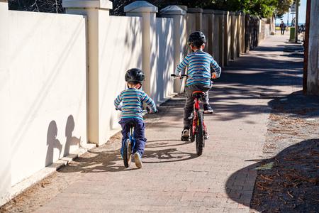 Children riding their bicycles towards Glenelg beach, South Australia Stock Photo