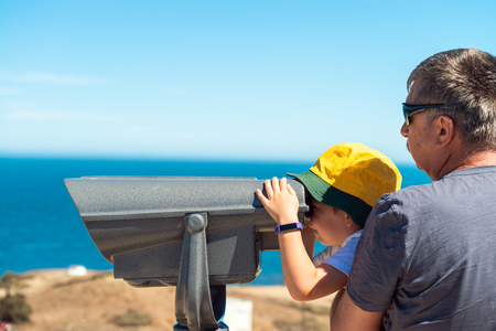 Grandfather and grandson observing Kangaroo Island coast scenery through outdoor binocular from Cape Jervis, South Australia.