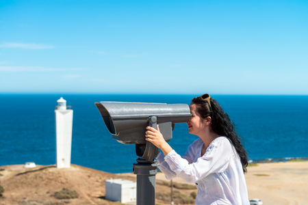 Pretty young woman  observing Kangaroo Island coast scenery through outdoor binocular from Cape Jervis, South Australia.