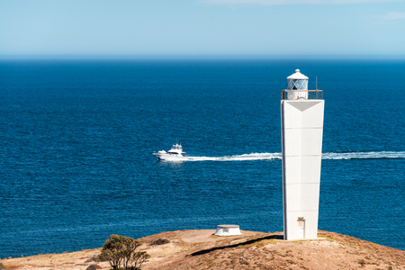 Cape Jervis Lighthouse with fishing boat  viewed from lookout, Fleurieu Peninsula, South Australia Stock Photo