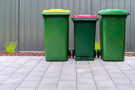 Australian home outdoor bins set provided by local council placed on backyard of suburban house Reklamní fotografie