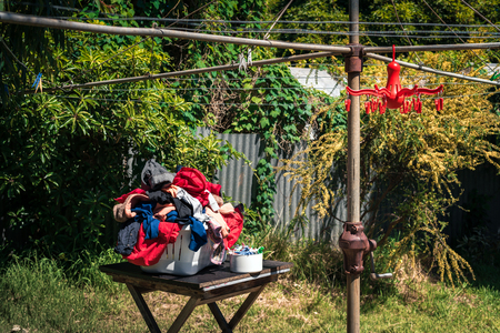 Panier à linge plein de tissu prêt à être accroché sur des cordes à linge rotatives australiennes sur l'arrière-cour
