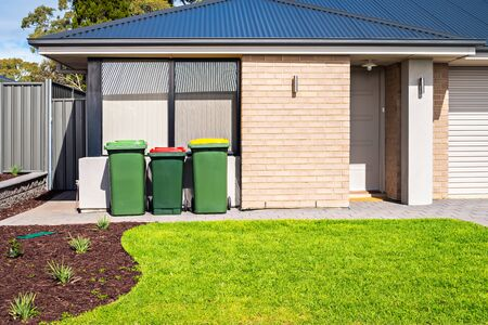 Brand new Australian suburban house with waste bins at the front yard