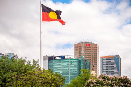 Adelaide CBD, Australia - November 18, 2017: Australian Aboriginal flag waving above city skyline viewed from Victoria Square on a day