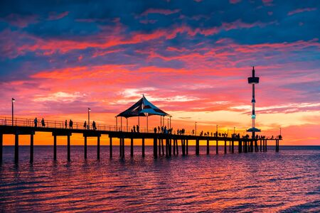 People walking along Brighton jetty with dramatic sunset on background after a hot summer day viwed from beach side, South Australia
