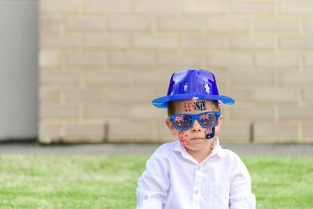 Serious Australian boy wearing sunglasses and hat while sitting on grass om front yard during Australia Day celebration