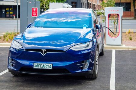 Adelaide CBD, Australia - November 18, 2017: Tesla Model X car connected to Supercharger EV charging station in city centre on Franklin Street on a day