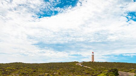 Cape Du Couedic lighthouse under beautiful sky next to waving road with SUV driving by, Kangaroo Island