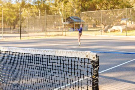 Close-up photo of outdoor tennis court net corner with player blurred in backgroud