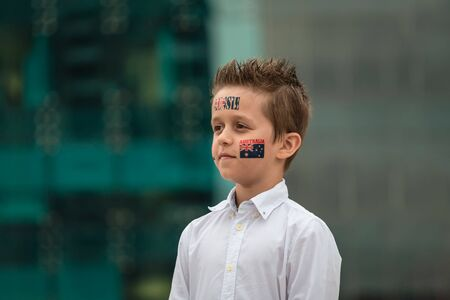 Portrait of proud Aussie boy with flag themed tattoos standing during Australian National Anthem during Australia Day celebration