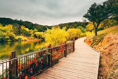 Scenic boardwalk around the pond at Mount Lofty botanic garden during autumn season, Adelaide Hills, South Australia Stock Photo