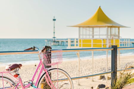 Pink classic bicycle with basket parked at Brighton Beach on a day, South Australia Фото со стока