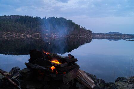 Camp fire besides a still lake Stock fotó