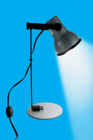 The Desk lamp on,isolated on blue background  photo