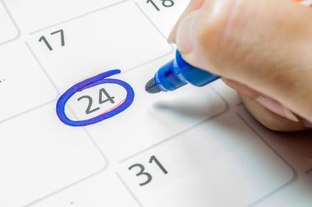 Blue color writing on the calendar at 24. Standard-Bild
