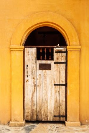 Brown wooden door on a building in orange. photo