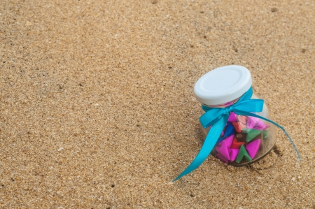 Paper heart in a glass bottle. Placed on the sand recycled paper craft fold. Stock Photo - 17358602