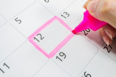 Pink color. Mark on the calendar at 12. Stock Photo
