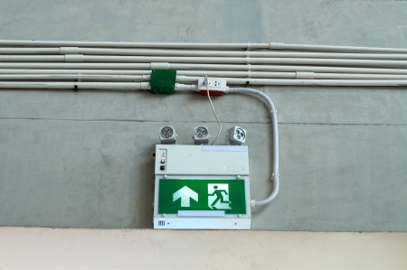 Green exit emergency sign on white wall photo