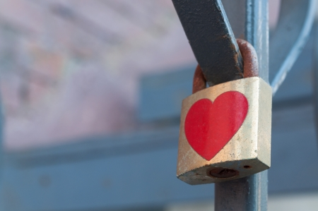 heavy heart: A lock with a heart shaped sticker with red lace. Stock Photo