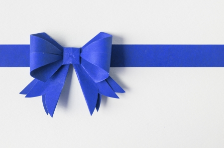 gift background: Blue ribbon on white recycled paper. Paper craft .