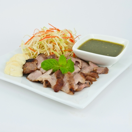 Pork with Lemon Sauce and Vegetables on the white plate photo