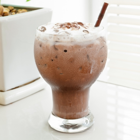 Chocolate smoothie in glass on white background.
