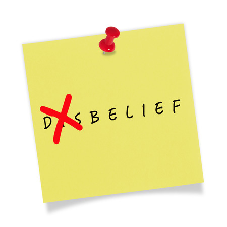 Yellow paper with red pin on white background. Belief. photo