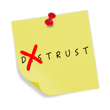 Yellow paper with red pin on white background. Changing the word distrust to trust. photo