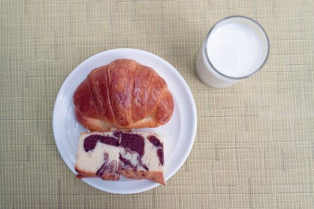 Bread Croissant on a white plate And milk on the yellow cream table Banco de Imagens