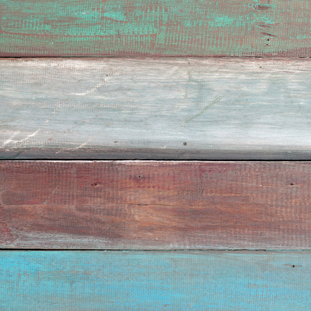 Old brown wooden background with white green and blue stripes.
