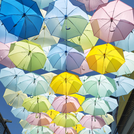 Umbrella yellow, blue, pink, green, hanging beautifully adorned. Banco de Imagens